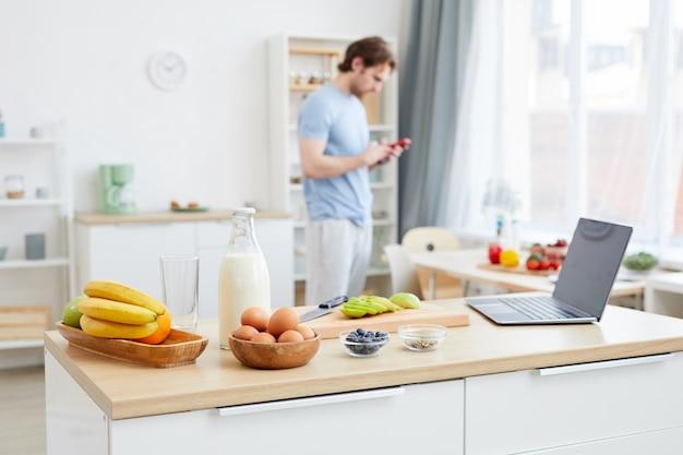 Mesa de cozinha com comida diferente e laptop preparado para o café da manhã com o homem ao fundo