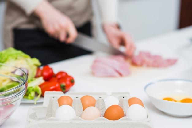 Mesa de cozinha com ingredientes e pessoa preparando comida