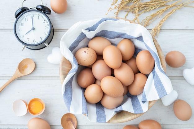 Mesa de cozinha com ovos crus, ovos de gema amarela, sinal de forma de coração branco e vintage clássico