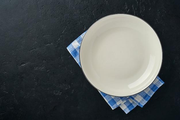 Mesa de cozinha com prato vazio de cor branca, toalha de mesa azul e espaço para sua receita ou menu.