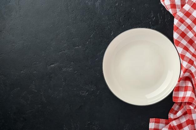Mesa de cozinha com prato vazio de cor branca, toalha de mesa vermelha e espaço para sua receita ou menu.