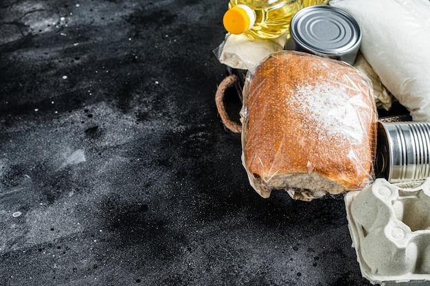 Mesa de cozinha com produtos alimentares de doação, conceito de ajuda de quarentena. óleo, comida enlatada, macarrão, pão, açúcar, ovo. fundo preto. vista do topo. copie o espaço.