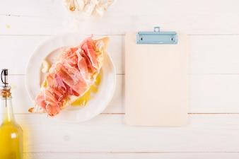 Mesa de cozinha com sanduiche e prancheta