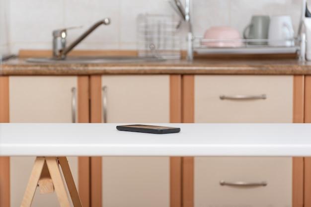 Mesa de cozinha e celular no fundo da cozinha. smartphone esquecido