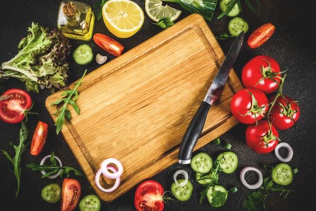Mesa de cozinha, ingredientes de salada fresca, cozinha italiana - tomate, azeite, limão, pepino, rúcula, salsa, cebola, com faca e tábua, vista de mesa enferrujada escura