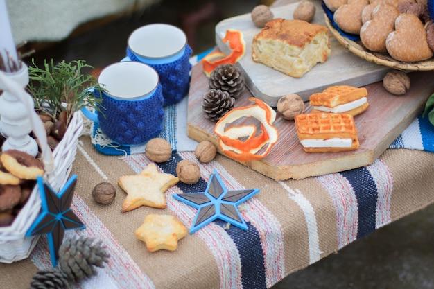 Mesa de decoração de inverno doce. canecas com cacau. doces e nozes