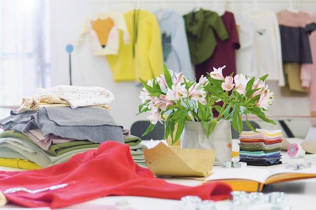 Mesa de designer de moda criativa ou local de trabalho com equipamentos de costura, tecidos, modelos, escritório de inspiração estilista moderna, atelier de costureira com roupas