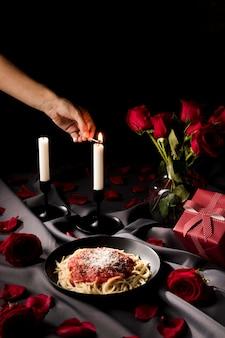 Mesa de dia dos namorados em ângulo elevado com velas e macarrão