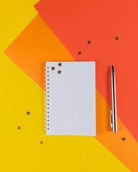 Mesa de escritório amarela e laranja com caderno em branco e outros materiais de escritório