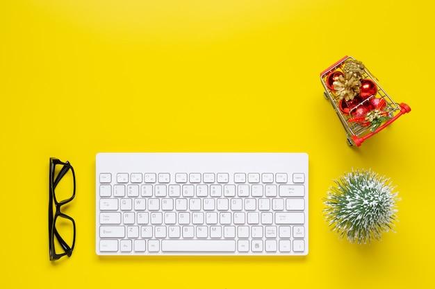 Mesa de escritório amarelo com enfeites de natal no carrinho de compras