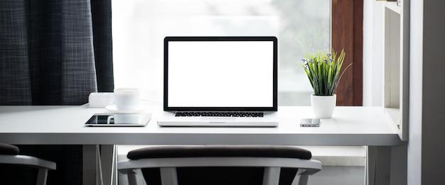 Mesa de escritório ao lado de uma janela com laptop e tablet pc