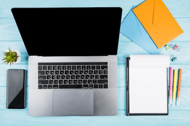 Mesa de escritório azul com laptop e materiais escolares