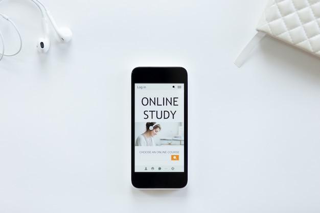 Mesa de escritório branca com fones de ouvido, telefone celular, estudo on-line na tela