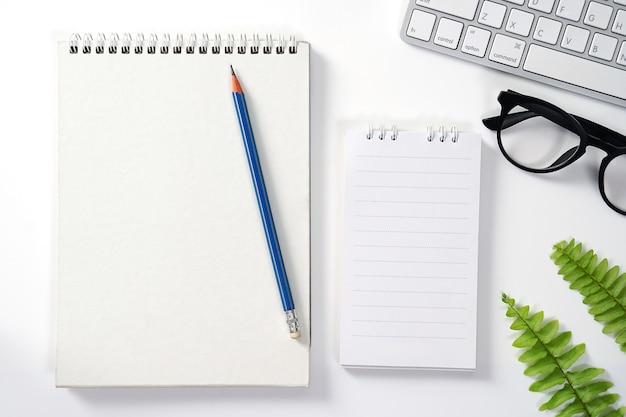 Mesa de escritório branca com lápis do bloco de notas do computador folha verde e outros suprimentos