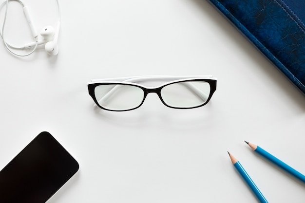 Mesa de escritório branca com óculos, lapis, fones de ouvido e celular