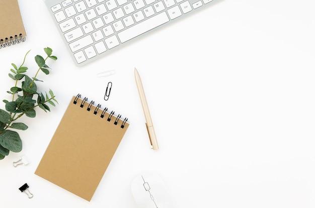 Mesa de escritório branca com teclado, caderno espiral e uma planta