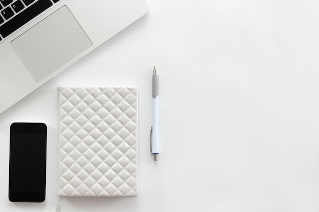 Mesa de escritório branca com uma parte de laptop, celular, caneta