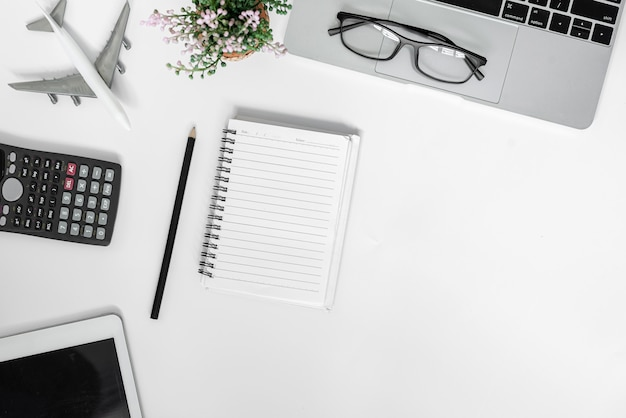 Mesa de escritório branca. mesa com caderno em branco, tablet, calculadora, computador e outros suprimentos de escritório