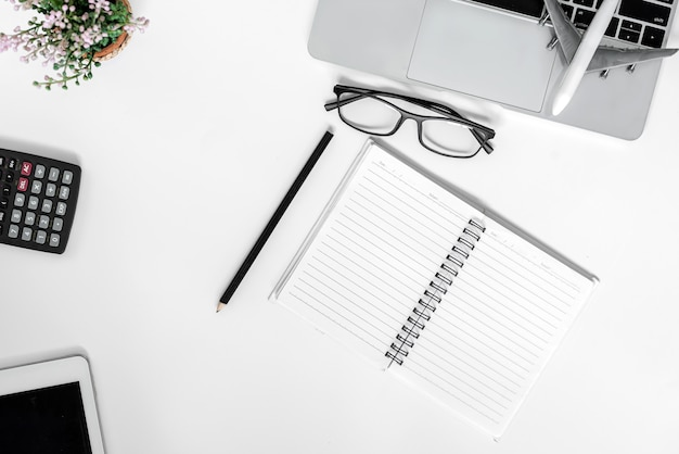 Mesa de escritório branca. mesa com caderno em branco, tablet, óculos, calculadora, computador e outros suprimentos de escritório. vista superior com espaço de cópia.