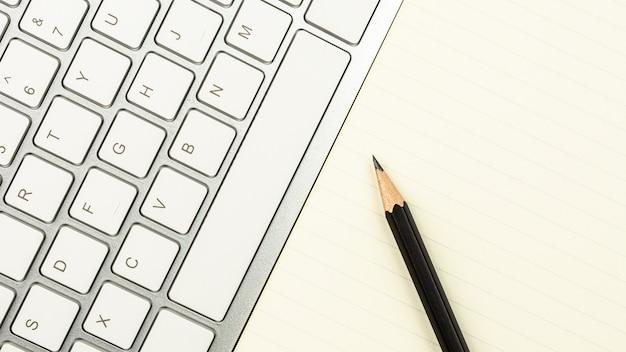 Mesa de escritório branca moderna com um teclado de computador, caneta e um notebook