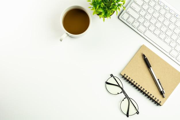 Mesa de escritório branca moderna com um teclado de computador, uma pena, um caderno e uma xícara de café.