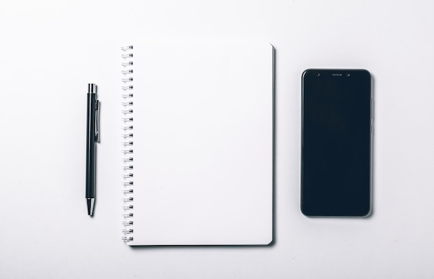 Mesa de escritório branco com caneta e telefone inteligente.