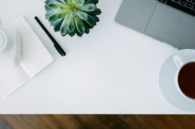 Mesa de escritório branco com laptop, planta e notebook com caneta, câmera e xícara de chá