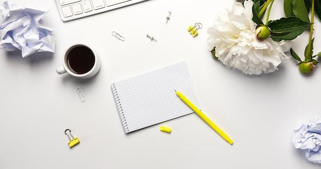Mesa de escritório branco com notebook, teclado em fundo branco