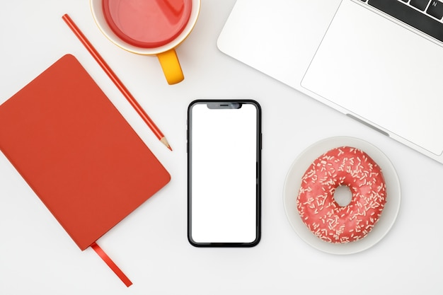 Mesa de escritório branco com tela em branco do smartphone