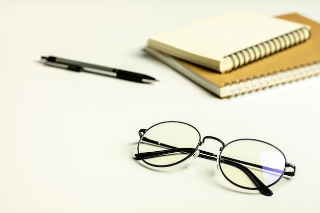 Mesa de escritório branco com um óculos, caneta e um caderno em branco.
