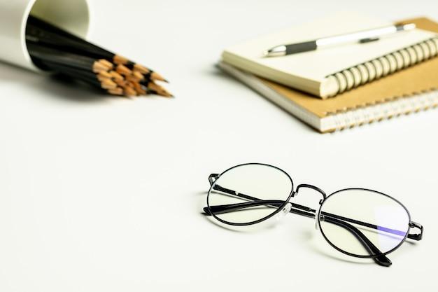 Mesa de escritório branco com um óculos, lápis e um caderno em branco.