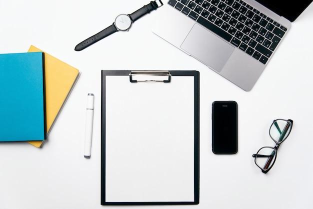 Mesa de escritório branco de vista superior com laptop, telefone, caderno, espaço em branco claro de papel com espaço de cópia gratuita e suprimentos, plano de fundo leigo.
