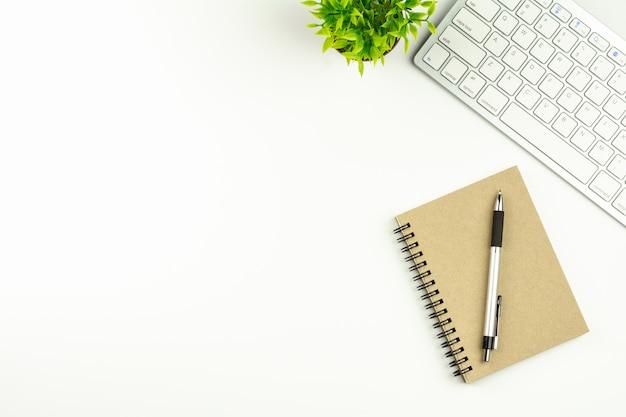 Mesa de escritório branco moderno com um teclado de computador, caneta e um notebook.