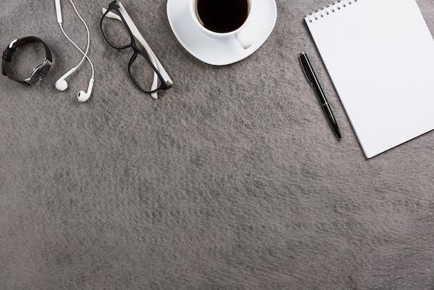 Mesa de escritório cinza com fone de ouvido; óculos; relógio de pulso; xícara de café; caneta e bloco de notas espiral em branco