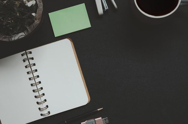 Mesa de escritório com bloco de notas, café, folha e caneta em fundo preto