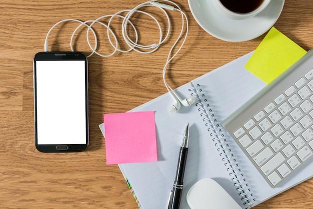 Mesa de escritório com bloco de notas, computador, xícara de café, mouse de computador, caneta, smartphone, pegajoso n