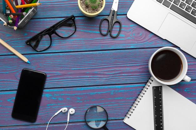 Mesa de escritório com bloco de notas em branco, laptop e material de escritório vista superior
