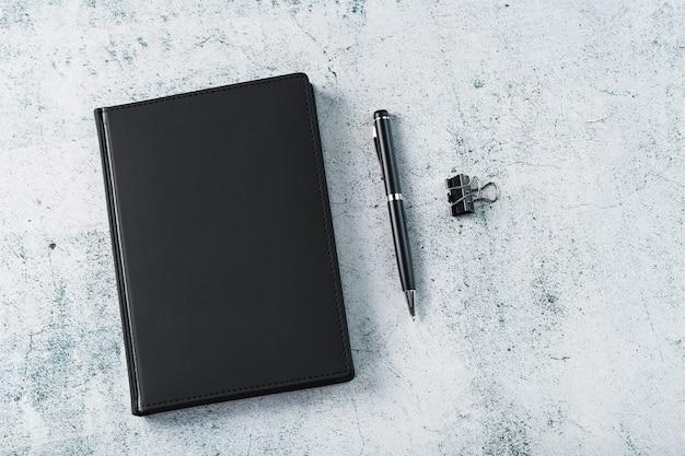 Mesa de escritório com bloco de notas preto e caneta em fundo cinza
