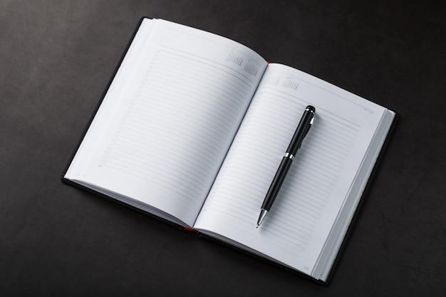 Mesa de escritório com bloco de notas preto e caneta sobre fundo preto. vista superior com espaço de cópia. conceito de metas e objetivos de negócios