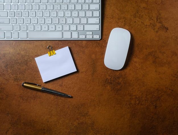 Mesa de escritório com bloco de notas, teclado de computador, mouse e caneta. vista de cima.