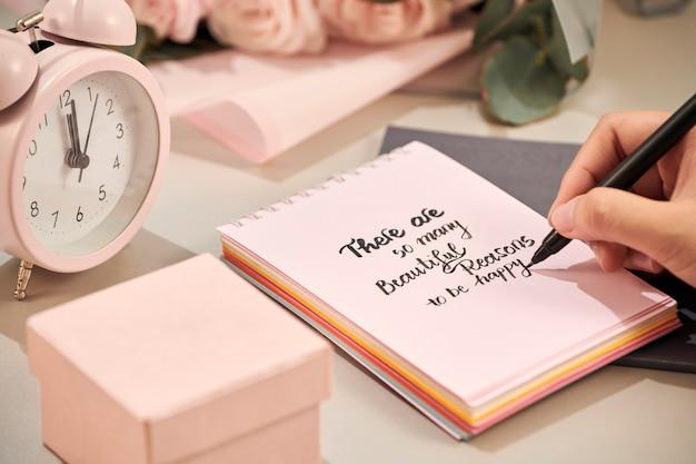 Mesa de escritório com caderno, lindo buquê de rosas rosa Foto Premium