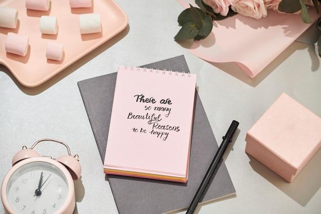 Mesa de escritório com caderno, lindo buquê de rosas rosa