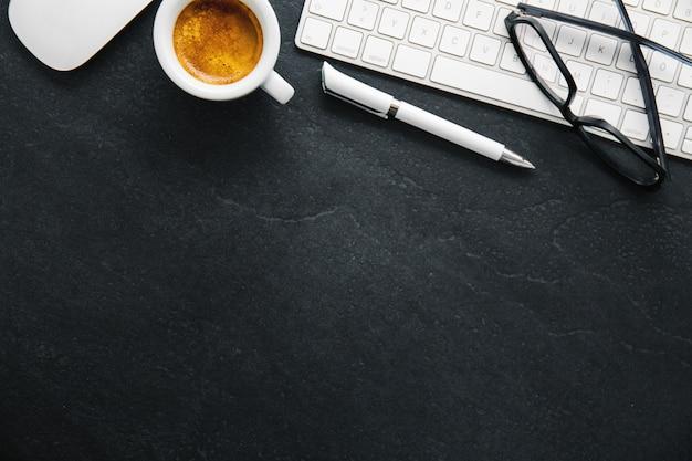 Mesa de escritório com café, teclado e bloco de notas
