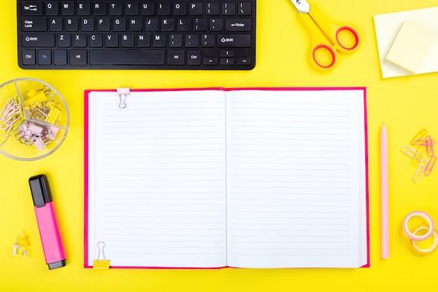 Mesa de escritório com computador e artigos de papelaria, fundo amarelo.