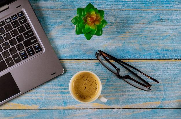 Mesa de escritório com computador e xícara de café, óculos ver os de cima.