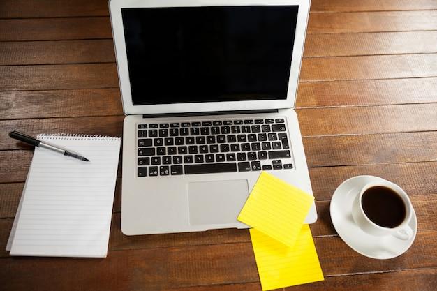 Mesa de escritório com computador portátil, bloco de notas e chávena de café