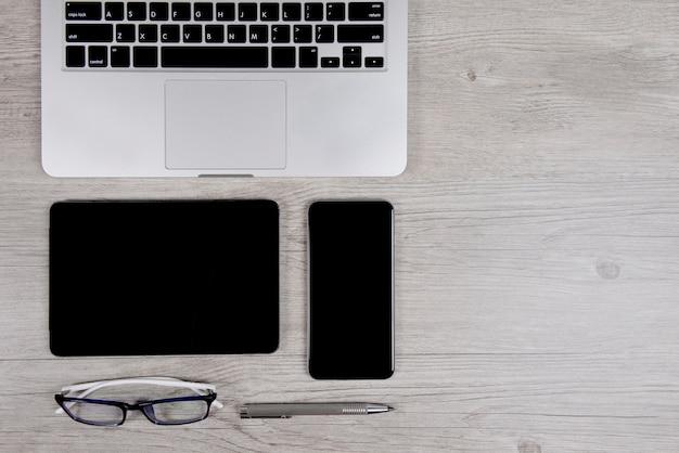 Mesa de escritório com computador portátil, notebook, tablet digital e smartphone na madeira est