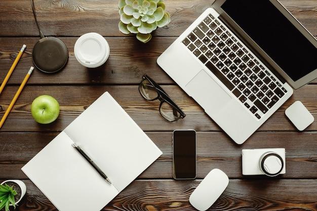 Mesa de escritório com computador portátil, suprimentos e maçã verde, vista superior