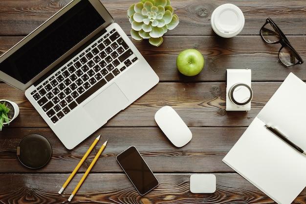 Mesa de escritório com computador portátil, suprimentos e maçã verde