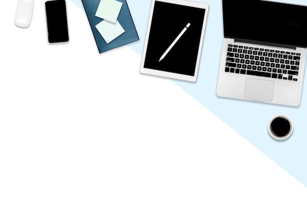 Mesa de escritório com computador portátil, tablet digital, telefone celular e acessórios.